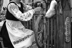 Young woman spinning thread on a spinning wheel. Black-and-white Stock Image