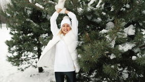 Young woman spinning in white winter clothes near a large pine stock footage