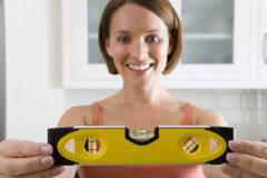 Young woman with spirit level, smiling, portrait, close-up of hands Stock Photos