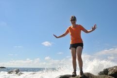 Young woman splashed by sea wave Stock Image