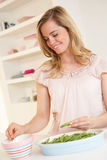 Young woman splitting pea in kitchen Stock Photography