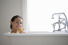Young woman with sponge in bath, smiling, portrait. Young women with sponge in bath, smiling, portrait Stock Image