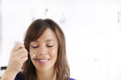 Young woman with spoon on lips. Young woman with spoon between lips smiling and looking in camera Stock Photos