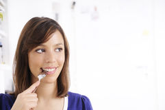 Young woman with spoon on lips Royalty Free Stock Image