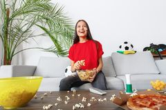 Young woman sport fan watching match in a red t-shirt excited stock photography