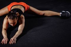 Woman sport stretching in gym with brick wall and black mats stock photo