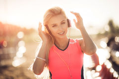 Young woman in sport wear enjoys and smiles listening music with orange earphones. She puts her hands up enjoying life. Royalty Free Stock Image