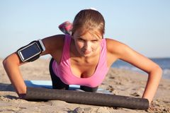Young woman sports on the beach. Young woman does sports exercises on the beach Royalty Free Stock Photography