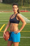 Young Woman in Sports Bra Holding Football with Hand on Hip Royalty Free Stock Images