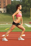 Young Woman in Sports Bra Stre. Beautiful Young Woman in Sports Bra Stretching Calf Muscles Royalty Free Stock Images