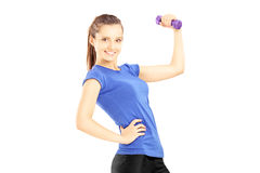 Young woman in sports outfit lifting a dumbbell. Isolated on white background Royalty Free Stock Photo