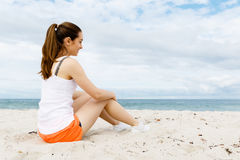 Young woman in sports wear sitting at the beach Royalty Free Stock Photo