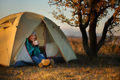 Young woman in sports wear and trekking shoes sitting in bivouac Royalty Free Stock Image