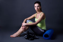 Young woman in sports wear with yoga mat and dumbbells over grey Stock Images