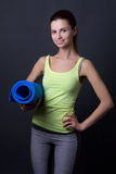 Young woman in sports wear with yoga mat over grey Royalty Free Stock Photo