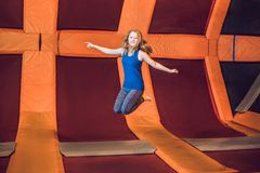 Young woman sportsman jumping on a trampoline in fitness park an royalty free stock image