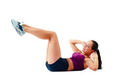 Young woman in sportswear does exercises lying on floor Stock Image