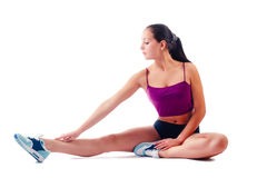 Young woman in sportswear does exercises sitting on floor Stock Image