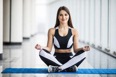 Young woman in sportswear doing meditation while standing in front of window at gym. Young beautiful woman in sportswear doing meditation while standing in front Royalty Free Stock Photography