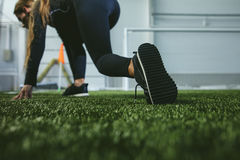 Young woman in sportswear is engaged in the sports stadium close Stock Photography
