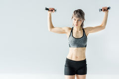 Young woman in sportswear exercising with dumbbells on grey Royalty Free Stock Photography