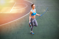 Young woman in sportswear exercising with skipping rope on stadium Royalty Free Stock Photo