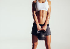 Young woman in sportswear holding a kettle bell Stock Image