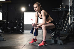 Young woman in sportswear holding towel and bottle of water in gym Royalty Free Stock Photo