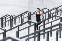 Young woman in sportswear jogging on stadium stairs Royalty Free Stock Photography
