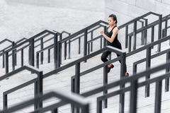 Young woman in sportswear jogging on stadium stairs Royalty Free Stock Photo