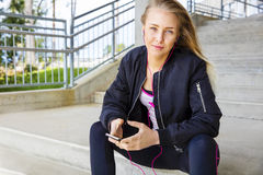 Young Woman In Sportswear Listening Music On Smartphone Royalty Free Stock Photography