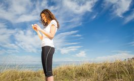 Young woman with sportswear looking her smartphone Royalty Free Stock Photography