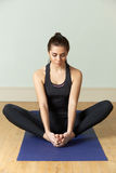 Young Woman In Sportswear Meditating On Mat Stock Photo