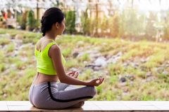 Young woman in meditating while sitting in lotus pose. Young woman in sportswear meditating while sitting in lotus pose Royalty Free Stock Image
