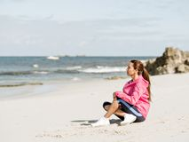 Young woman sitting at the beach in sportswear. Young woman in sportswear sitting at the beach Stock Photo