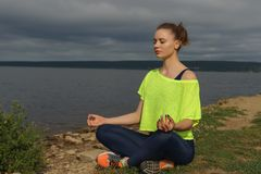 Young woman in sportswear sitting on river shore stock photography