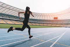 Young woman in sportswear sprinting on running track stadium at sunset. Athletic young woman in sportswear sprinting on running track stadium at sunset Stock Photography