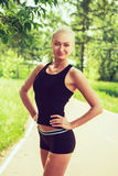 Young woman in sportswear standing outdoors in a park on sunny s Royalty Free Stock Photos