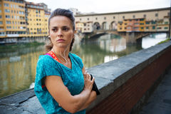 Young woman in sportswear is staying next to Ponte Vecchio Stock Photos