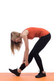 Young woman in sportswear training back and leg on a orange mat Stock Photo