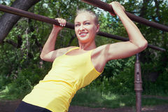 Young woman in sportswear working out outdoors in a park on sunn Stock Image