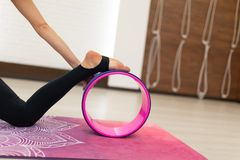 Young woman in a sportswear yoga exercises with a yoga wheel in the gym. Stretching and wellness lifestyle.  stock image