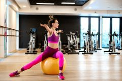 Young woman in sportwear sport exercise wit yellow fitball in gym. Fitness and wellness lifestyle concept.  stock images