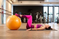 Young woman in sportwear sport exercise wit yellow fitball in gym. Fitness and wellness lifestyle concept. Girl in sportwear sport exercise wit yellow fitball in royalty free stock photo