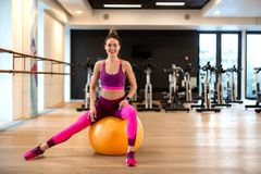 Young woman in sportwear sport exercise wit yellow fitball in gym. Fitness and wellness lifestyle concept.  stock image