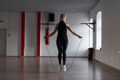 Young woman in sporty black leggings in stylish sneakers does jump rope in a gym. Girl goes in for sports in a fitness studio. Cardio training stock photos