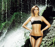 Young woman with a sporty body near a waterfall Royalty Free Stock Image