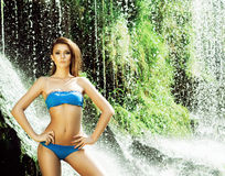 Young woman with a sporty body next to a waterfall Stock Image