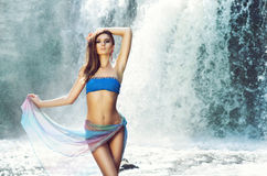 Young woman with a sporty body next to a waterfall Stock Photography