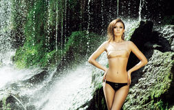 Young woman with a sporty body next to a waterfall Stock Photos